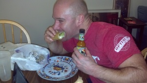 """Forney eating a Taco Bell """"ultimate recovery"""" meal: 2 Chalupa Supremes and a Grilled Stuffed Burrito, smothered in scotch bonnet pepper sauce."""